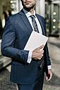 Handsome businessman walking in Manhattan, carrying digital tablet - GIOF02051