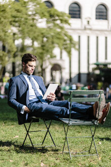 Businessman in Manhattan sitting on garden chair using digital tablet with feet up - GIOF02063