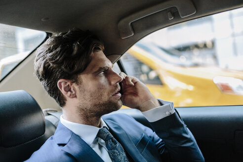 Businessman sitting in taxi, using smart phone - GIOF02084