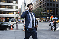 Handsone businessman in a hurry running through Manhattan, using smart phone - GIOF02093