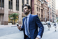 Handsone businessman in a hurry running through Manhattan, using smart phone - GIOF02096