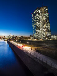 Germany, Frankfurt, lighted European Central Bank and skyline in the background at sunset - AMF05305