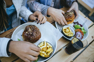 Women's hands eating Hamburgers and French fries - KIJF01302