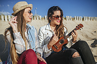 Two young women with ukulele sitting on the beach - KIJF01305