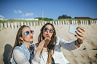 Two young women taking selfie on the beach while blowing a kiss - KIJF01308
