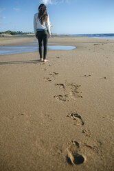 Back view of young woman walking on the beach leaving her footprints in the sand - KIJF01311