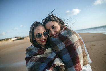 Portrait of two women covered with blanket on the beach - KIJF01314