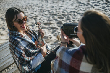 Smiling young woman playing ukulele while her friend recording with video camera - KIJF01320