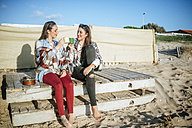Two young women drinking coffee on the beach - KIJF01323