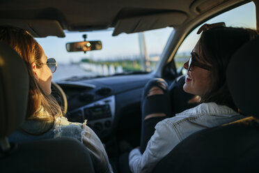 Two young women with sunglasses relaxing in car at evening twilight - KIJF01329