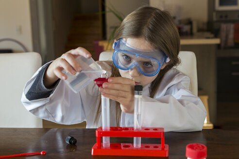 Girl wearing work coat and safety glasses using chemistry set at home - SARF03221