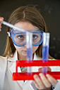 Portrait of girl wearing work coat and safety glasses doing chemical experiment - SARF03227