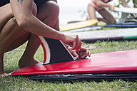 Woman preparing surfboard on meadow - KNTF00649