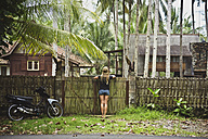 Indonesia, Java, back view of woman leaning on garden gate looking at houses - KNTF00653