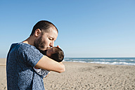 Father kissing his newborn baby girl on the beach - GEMF01520