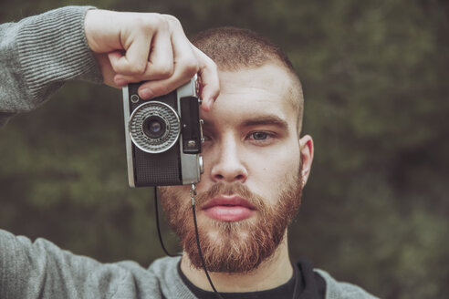 Portrait of bearded man taking photo with vintage camera - RTBF00719