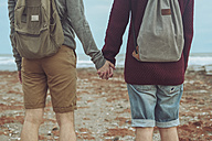Back view of young gay couple holding hands on the beach - RTBF00722