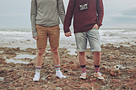 Young gay couple standing hand in hand on the beach, partial view - RTBF00725