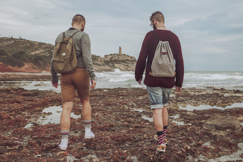Spain, Oropesa del Mar, two young men walking on stony beach - RTBF00728
