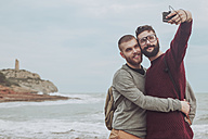 Spain, Oropesa del Mar, gay couple taking selfie in front of the sea - RTBF00734