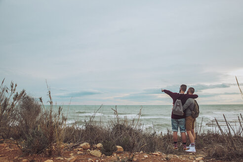 Back view of young gay couple looking at the sea - RTBF00740