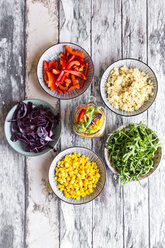 Glass of rainbow salad with bulgur, rocket and different vegetables and bowls with ingredients - SARF03240