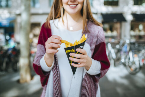 Young woman in Sevilla eating french fries - KIJF01339
