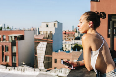 Young woman standing on rooftop in Brooklyn,looking at distance - GIOF02100