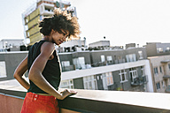 Young woman standing on rooftop in Brookliyn, looking down - GIOF02106
