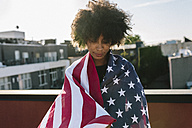 Young woman standing on rooftop warpped in US American flag - GIOF02118