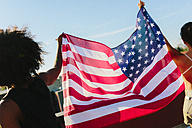Female friends holding US American flag, standing on rooftop - GIOF02121