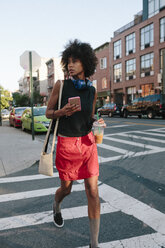 Young woman with headphones and smart phone crossong street in Brooklyn, carying take away drink - GIOF02130