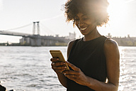 Young woman in Brooklyn standing at East River using smart phone - GIOF02133