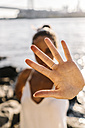 Young woman in Brooklyn standing at East River showing hand palm - GIOF02136