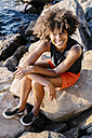 Young woman sitting on boulders at river - GIOF02139