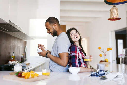 Young couple having breakfast in the kitchen, standing back to back - VABF01224