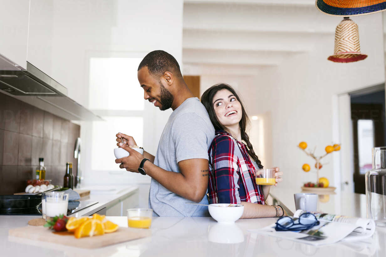 Young couple having breakfast in the kitchen, standing back to back - VABF01224 - Valentina Barreto/Westend61