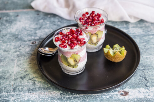 Two glasses of chia pudding with heart-shaped kiwi slices and pomegranate seed on tray - SARF03249