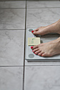 Woman standing on bathroom scales with sticky note of ideal weight - CHPF00372