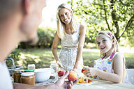 Happy family in garden preserving peaches - WESTF22778