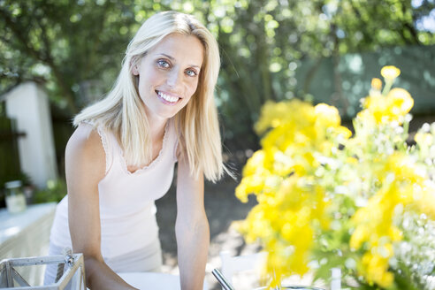 Smiling woman with flowers outdoors - WESTF22787