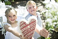 Smiling sister and brother holding heart and bunch of flowers - WESTF22799