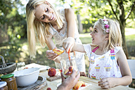 Smiling mother and daughter preserving peaches - WESTF22802