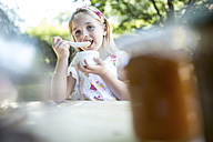 Girl eating at garden table - WESTF22805