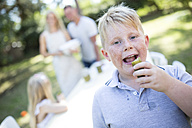 Portrait of boy eating gherkin outdoors with family in background - WESTF22817