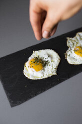 Eggs sunny side up with herbs on a slatte - GIOF02141