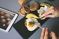 Breakfast with eggs, avovados and toasted bread on a table with digital tablet - GIOF02147