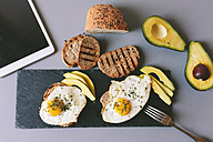 Breakfast with eggs, avovados and toasted bread on a table with digital tablet - GIOF02150