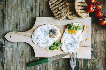 Eggs sunny side up on chopping board by tomatoes and toast - GIOF02168