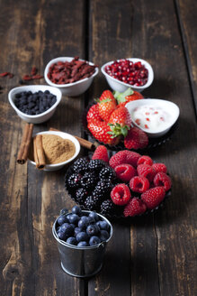 Various dried and fresh fruits and bowl of cinnamon powder with cinnamon sticks on wood - CSF27979